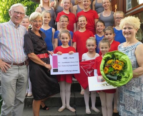 Dr. Johannes Bolten und Gabriele Willscheid, beide BürgerStiftungLohmar überreichen den Tänzerinnen einen stattlichen Scheck. Andrea Kaseler-Fegert, Jazz&Modern Dance Club dankt mit einem üppigen Blumenstrauß. (Foto: BürgerStiftungLohmar)